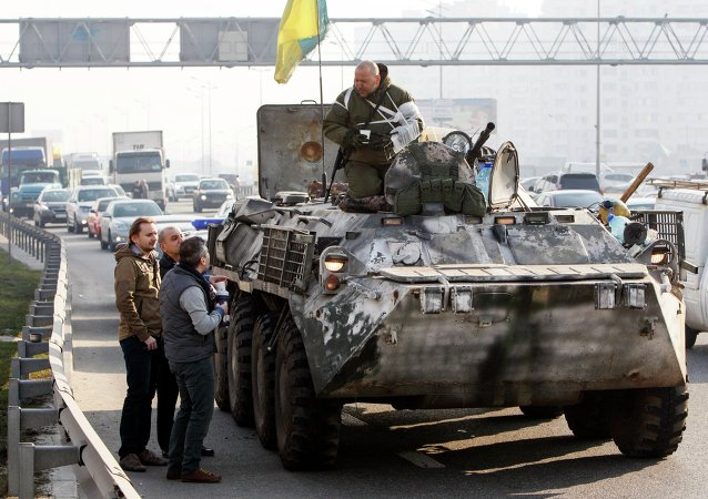 Civilians talk to Ukrainian serviceman who is returning from the front line in eastern Ukraine, in Kiev, March 11, 2015