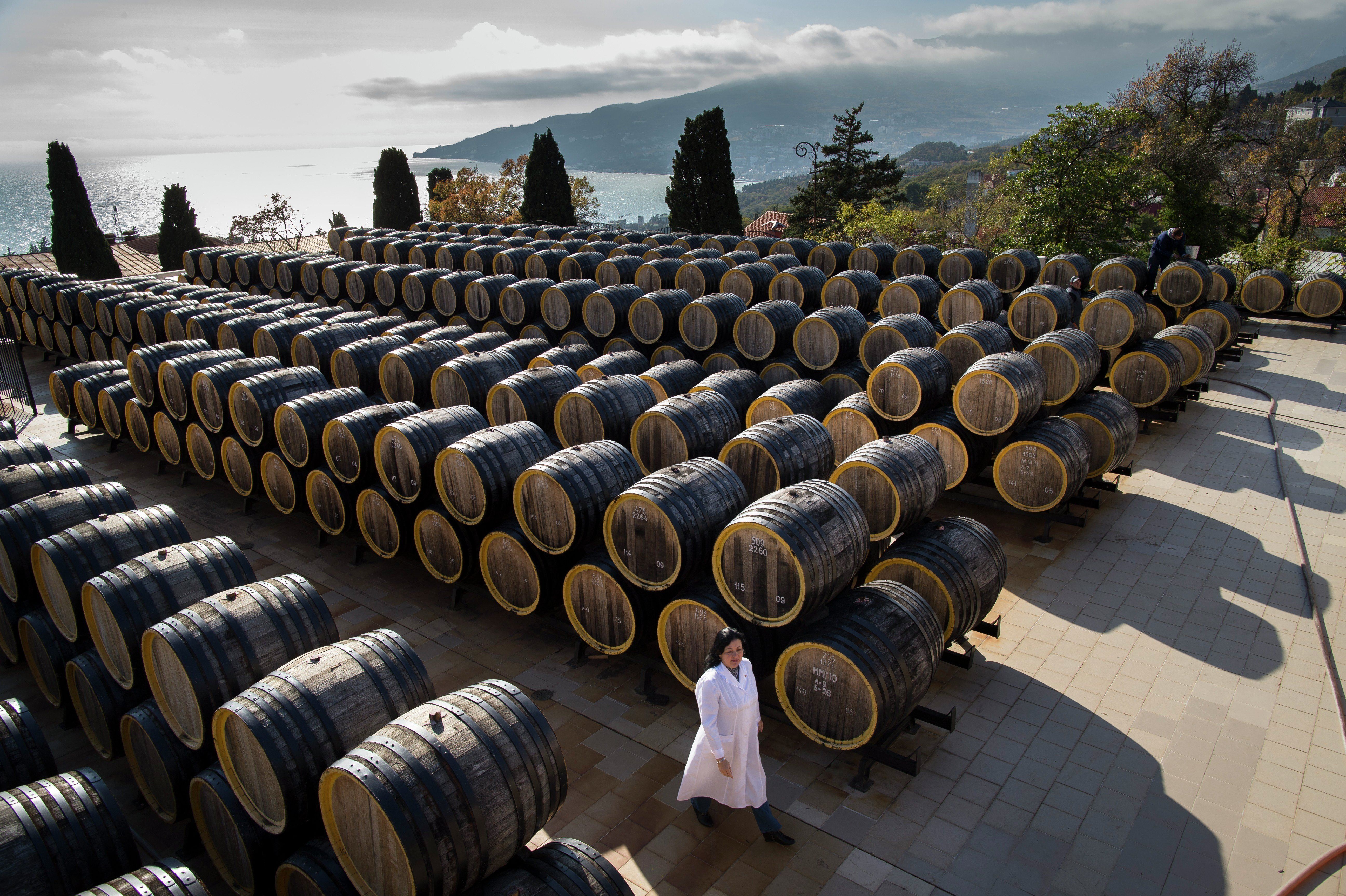 In this photo taken on Tuesday, Oct. 28, 2014, Rameta Kushkhova walks by barrels of wine in the state-owned Massandra winery in Yalta, Crimea