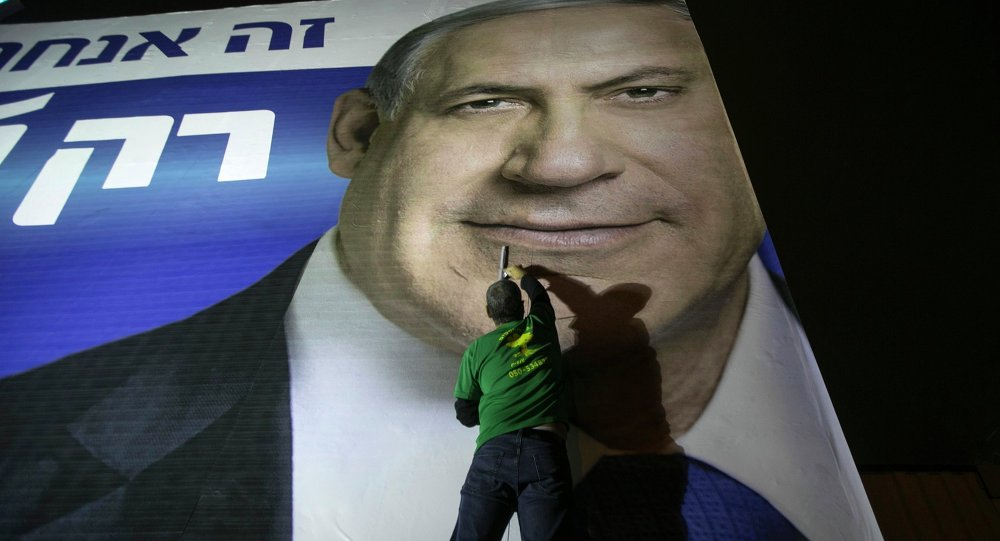 A worker installs a campaign poster of Israel's Prime Minister Benjamin Netanyahu on a billboard in Tel Aviv March 10, 2015