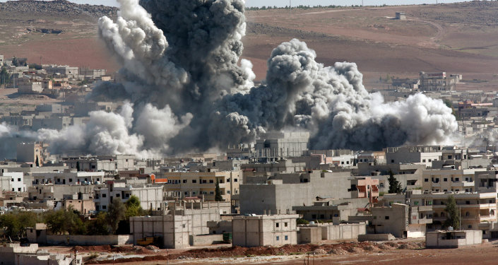 In this Monday, Nov. 17, 2014 file photo, smoke rises from the Syrian city of Kobani, following an airstrike by the U.S.-led coalition, seen from a hilltop outside Suruc, on the Turkey-Syria border.