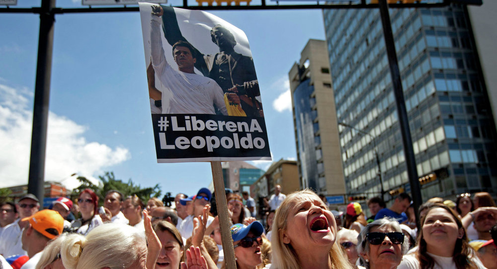 Supporters of jailed opposition leader Leopoldo Lopez chant slogans demanding his freedom and at an event marking the one year anniversary of his arrest and imprisonment in Caracas, Venezuela, Wednesday, Feb. 18, 2015