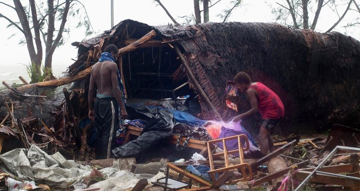 Local residents look through the remains of a small shelter in Port Vila, the capital city of the Pacific island nation of Vanuatu.