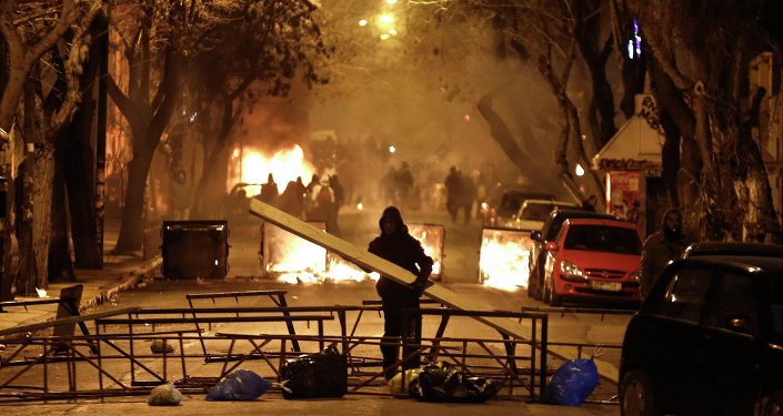 A masked youth places a wooden beam at a barricade during clashes with riot police in Athens March 17, 2015