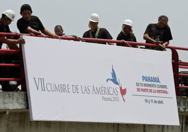 Workers install a banner announcing the upcoming 7th Summit of the Americas in Panama City