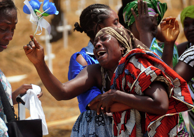 Relatives weep as they bury a loved one suspected of dying from the Ebola virus at a new graveyard on the outskirts of Monrovia, Liberia, March 11, 2015