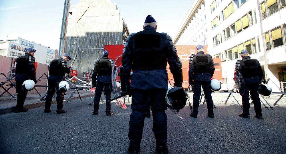 Riot police wait at a roadblock outside of an EU summit in Brussels