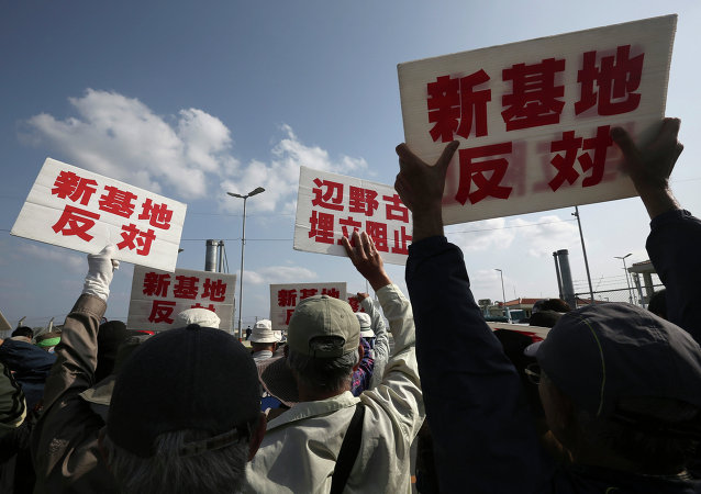 Protesters against the relocation of US Marine Corps Air Station Futenma, stage a rally in front of Camp Schwab, an American base near a planned relocation site, in Nago, Okinawa Prefecture Monday, March 23, 2015.