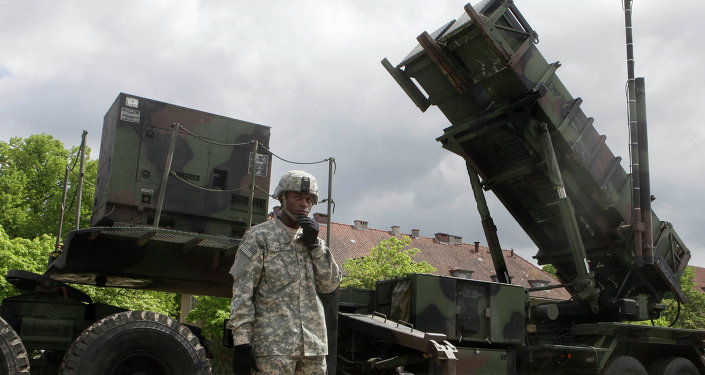 US soldier stands next to a Patriot surface-to-air missile battery at an army base in Morag, Poland
