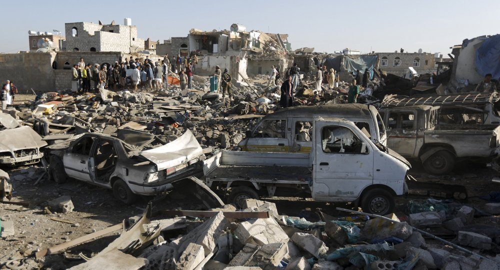 People gather at the site of an air strike at a residential area near Sanaa Airport March 26, 2015