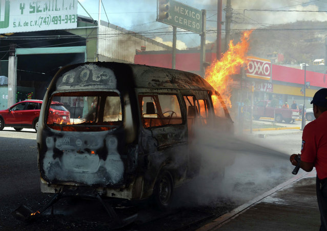 An emergency worker tries to extinguish a burning passenger van after protesters set it ablaze in the city of Chilpancingo, Mexico, Thursday, March 26, 2015