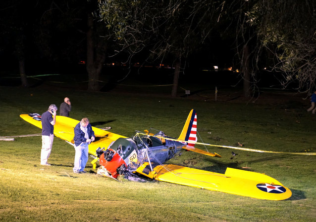 Officials work on the scene of a vintage airplane that crash-landed on the Penmar Golf Course in the Venice area of Los Angeles