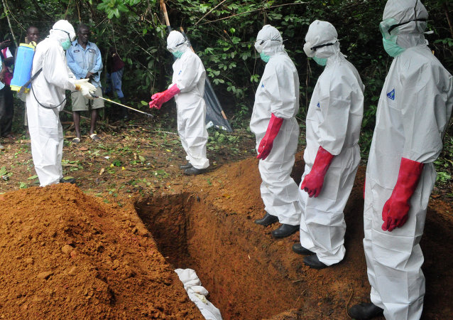A burial team in protective gear spray each other with disinfectant after burying the body of woman suspected to have died from Ebola virus in Monrovia, Liberia