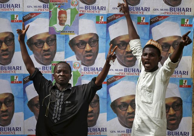 Supporters of presidential candidate Muhammadu Buhari gesture in front of his election posters in Kano
