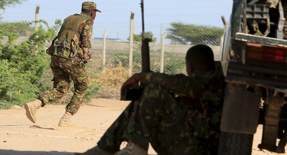 A Kenya Defense Force soldier runs for cover near the perimeter wall where attackers are holding up at a campus in Garissa April 2, 2015.