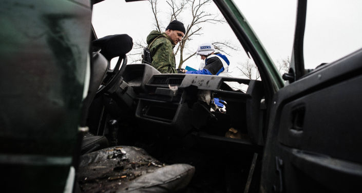 An armed man and an international observer of the Organization for Security and Co-operation in Europe (OSCE) stand next a destroyed car after shelling during an OSCE inspection tour near the village of Shirokino.