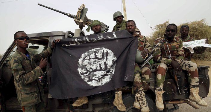 Nigerian soldiers hold up a Boko Haram flag that they had seized in the recently retaken town of Damasak, Nigeria, March 18, 2015