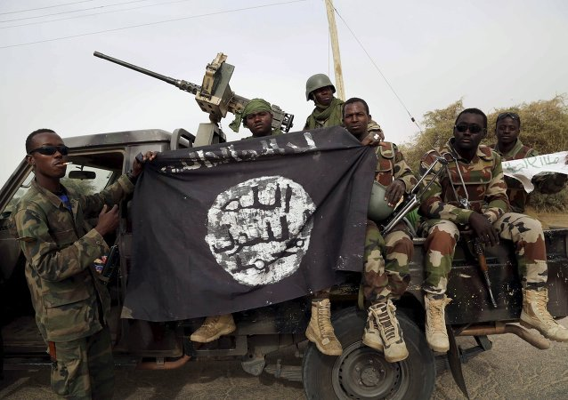 Nigerien soldiers hold up a Boko Haram flag that they had seized in the recently retaken town of Damasak, Nigeria, March 18, 2015