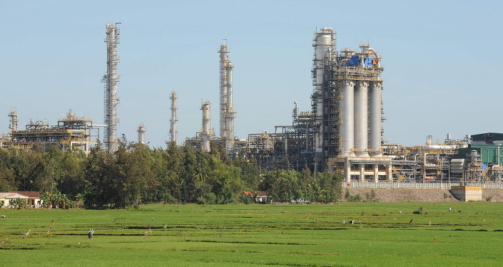 Vietnam's first oil refinery at Dung Quat looms over a rice field on February 22, 2009 in the central province of Quang Ngai