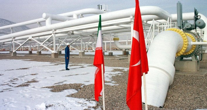 An Iranian worker stands in front of gas pipelines next to the flags of Turkey (R) and Iran