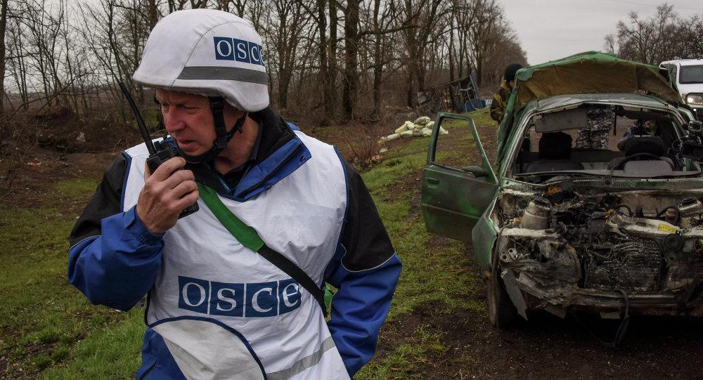 OSCE observers inspect a damaged car near Shyrokyne village, eastern Ukraine, Monday, March 30, 2015