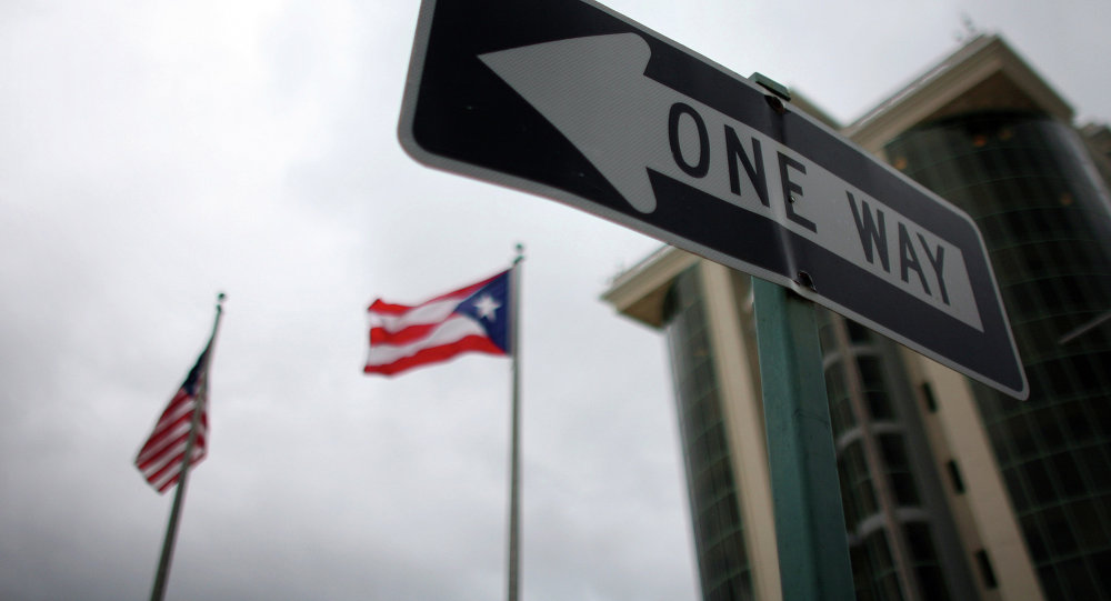 In this May 4, 2012 photo, the flags of Puerto Rico and the U.S. wave behind an English one-way traffic sign in Guaynabo, Puerto Rico, one of only a few places in Puerto Rico with street signs in English