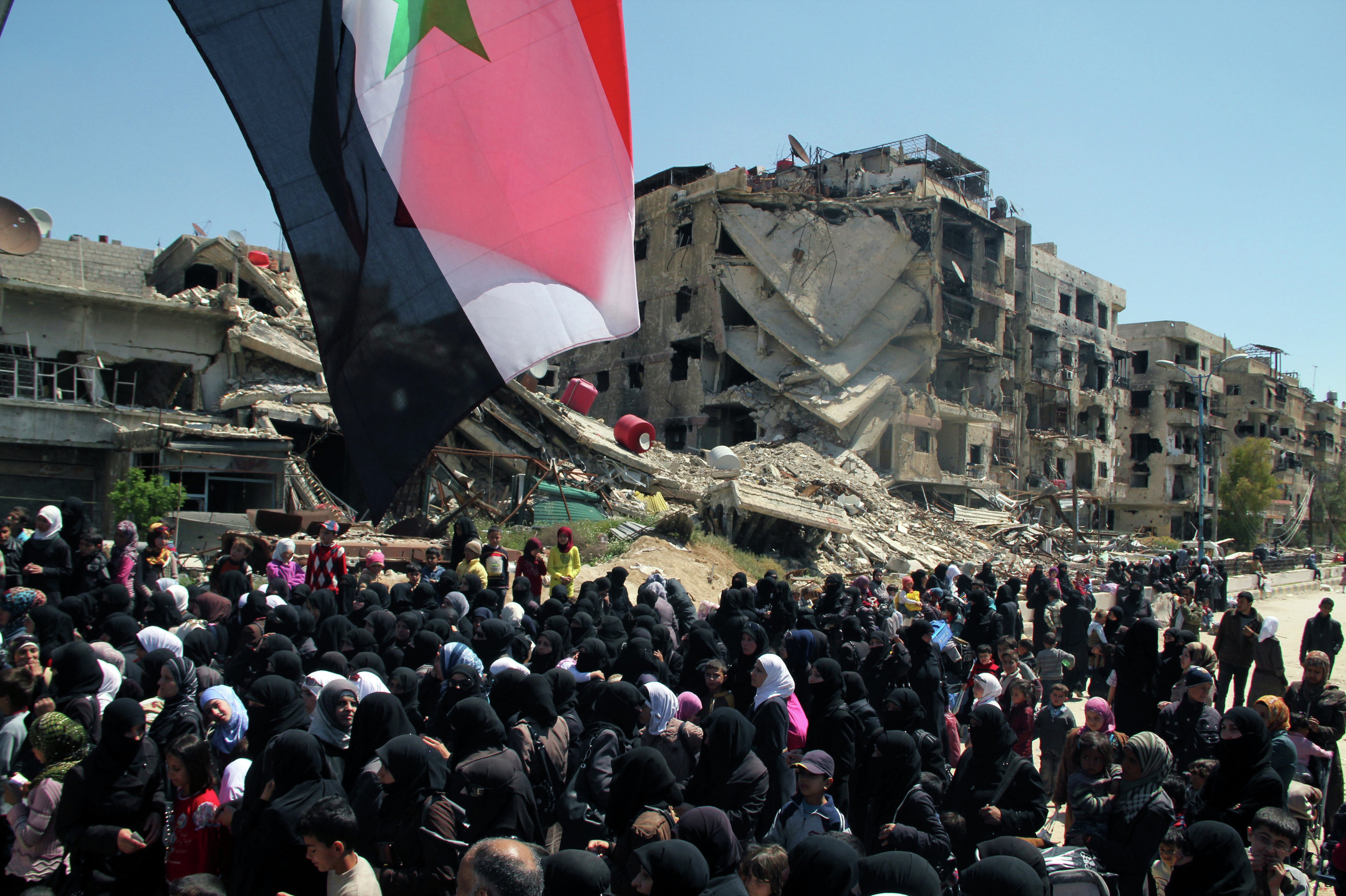 Residents flee the Palestinian refugee camp Yarmouk on the outskirts of Damascus. Clashes between Free Syrian Army fighters and ISIS militants have been going on in the district. Yarmouk residents wait in line to enter the territory controlled by the Syrian government