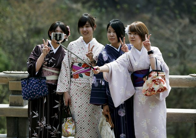 Kimono-clad women take selfies by using a selfie stick at Kiyomizu-dera Buddhist temple in Kyoto, western Japan