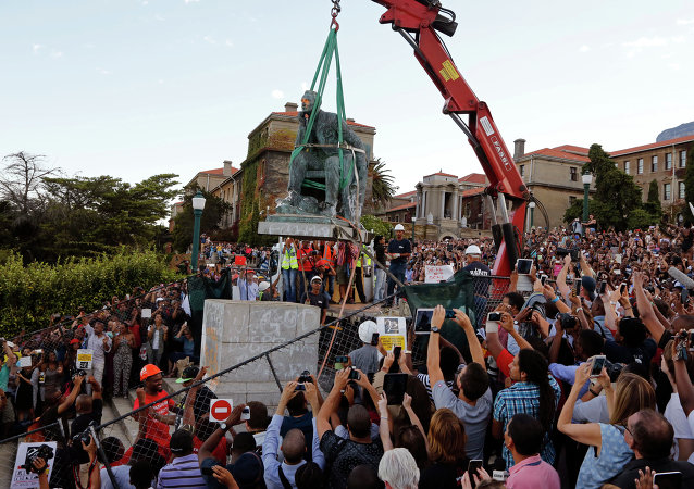 Cheering students surround the decades old bronze statue of British colonialist Cecil John Rhodes, as it is removed from the campus at the Cape Town University, Cape Town, South Africa, Thursday, April 9, 2015