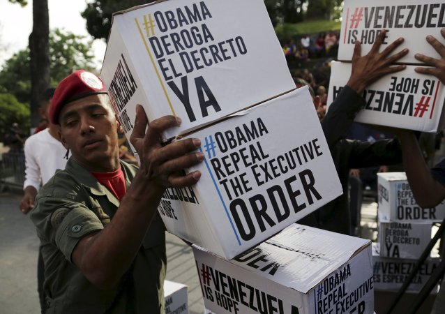 A Venezuela's soldier carries boxes containing signatures to ask U.S. President Barack Obama to lift sanctions against a group of Venezuelan army members before a rally at Miraflores Palace in Caracas