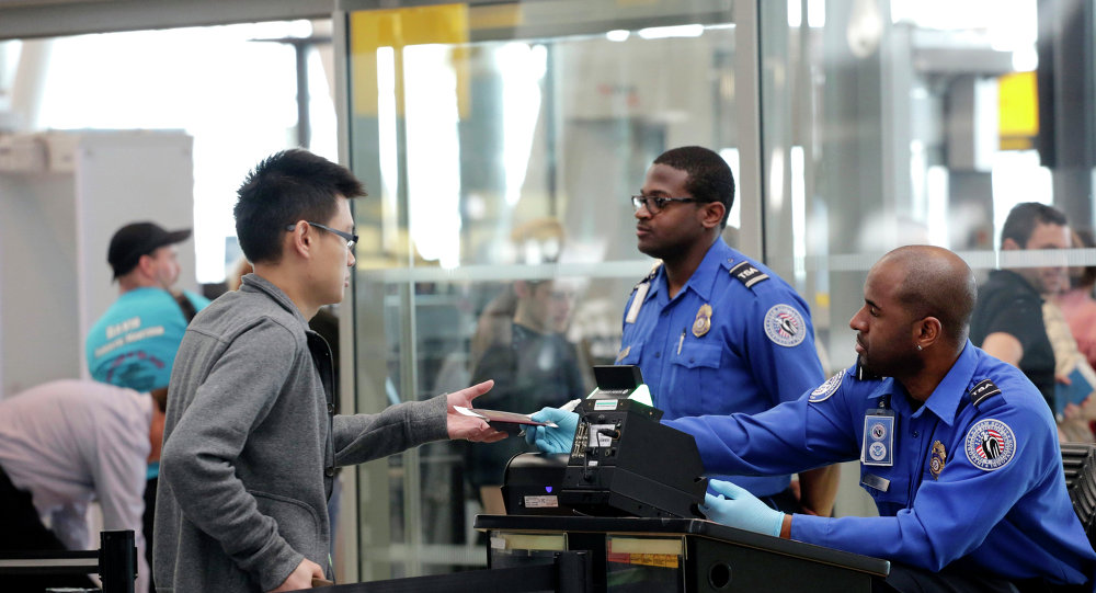 a traveler left hands his documents to a transportation security administration officer as part