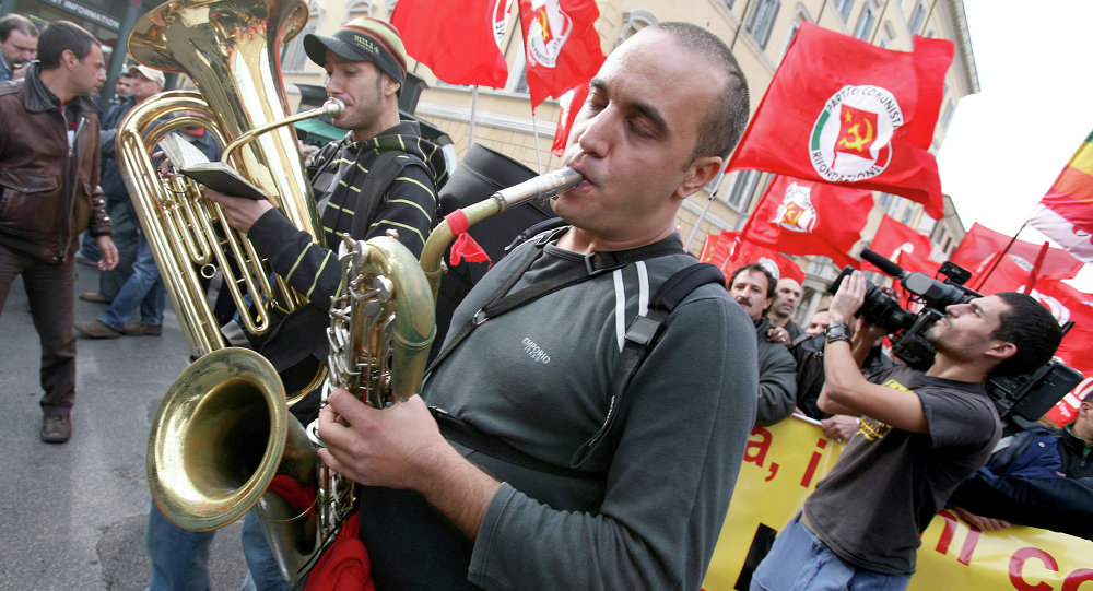 People play music as others hold Italian Communist Refoundation party flags during a demonstration in downtown Rome, Italy. (File)
