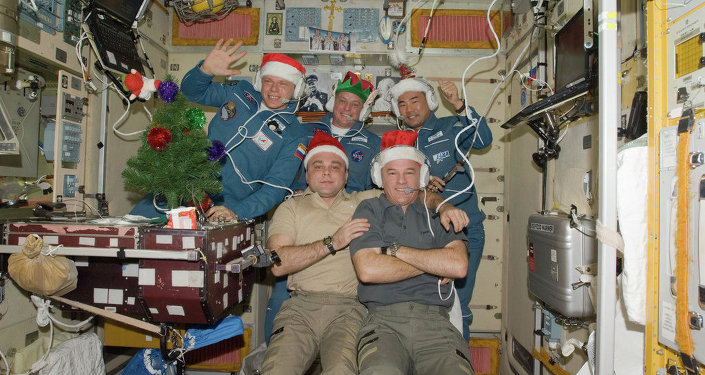 Wearing festive holiday hats, the Expedition 22 crew members are pictured while speaking with officials from Russia, Japan and the United States from the Zvezda Service Module of the International Space Station