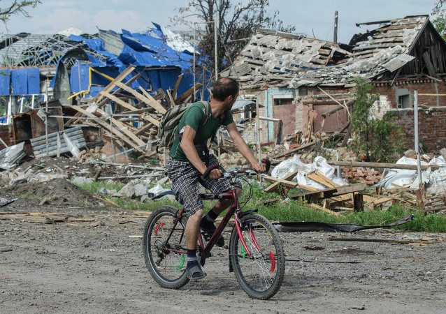 A local citizen rides a bicycle past destroyed houses after heavy fighting between independence supporters and Ukrainian government troops just outside Slovyansk, eastern Ukraine, Wednesday, July 9, 2014