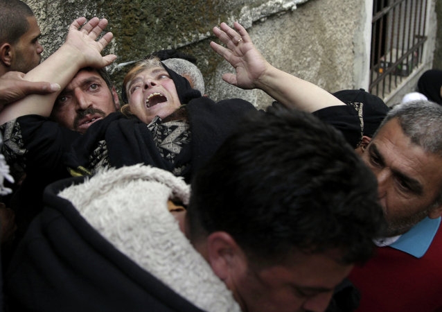 Mourners grieve during the funeral of Ziyad Awad during his funeral in Beit Ummar, West Bank, Friday, April 10, 2015