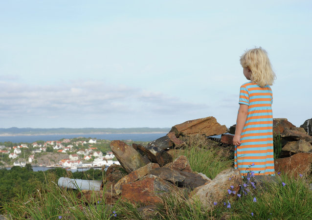 Girl standing at the hilltop Hoyfjellet at Flekkeroy in Kristiansand in Southern Norway.
