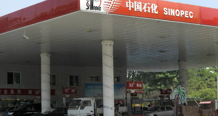 A man stands prepares to fill up his truck at a Sinopec's gas station in Beijing