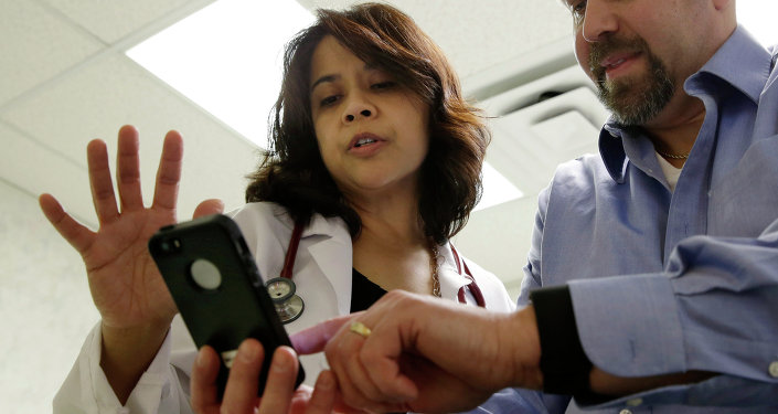 A doctor looks at data on a smart phone synchronized to a new Fitbit Surge worn by a patient.