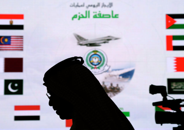 A Saudi man walks past a screen projecting images during a military briefing on the Saudi-led coalition's strikes in Yemen on Houthi rebels, in Riyadh, Saudi Arabia.