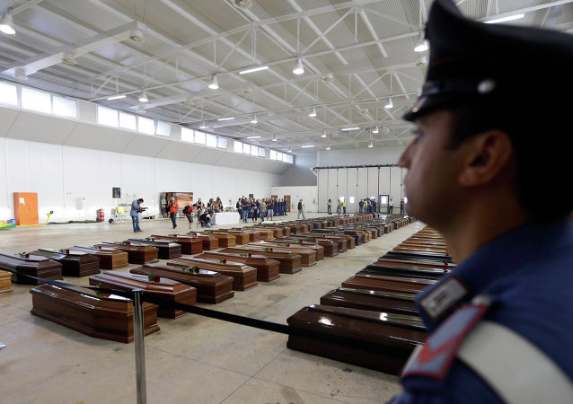 An Italian Carabiniere, paramilitary police man, stands near the coffins of died immigrants inside a hangar of Lampedusa's airport, Italy.