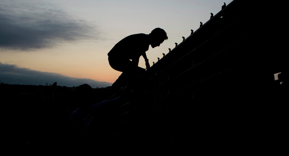 A migrant jumps to cross the U.S. Mexico border fence in Tijuana, Mexico, Thursday, Sept. 11, 2008.
