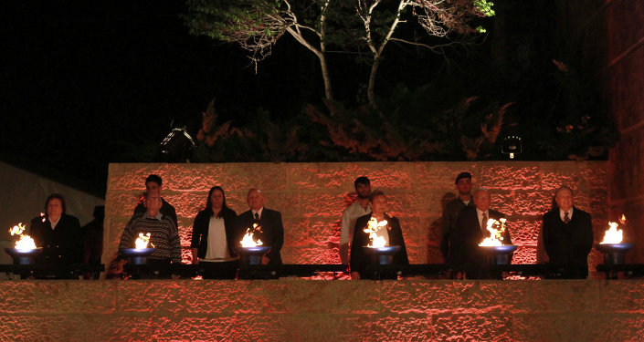 Holocaust survivors light six torches in memory of the victims during a ceremony marking the Holocaust Remembrance Day