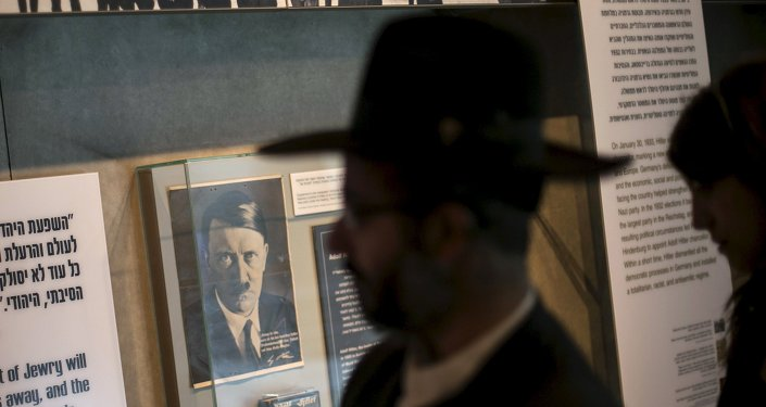 A visitor walks past a photograph of Adolf Hitler displayed at Yad Vashem's Holocaust History Museum in Jerusalem