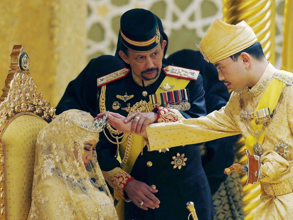 Brunei's Sultan Hassanal Bolkiah holds the arm of his son Prince Abdul Malik to bless Malik's new wife Dayangku Raabi'atul 'Adawiyyah Pengiran Haji Bolkiah during the bersanding or enthronement ceremony at their wedding in the Nurul Iman Palace in Bandar Seri Begawan April 12, 2015. Brunei's Sultan Hassanal Bolkiah is one of the world's richest men.