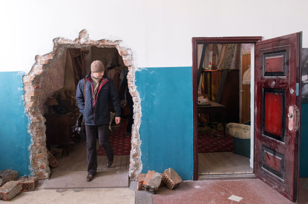 A man inspects an installation representing a damaged apartment in eastern Ukraine at the exhibition Material Evidence. Donbass. 365 Days in Moscow on April 13, 2015. The exhibition focuses on the armed conflict in eastern Ukraine.