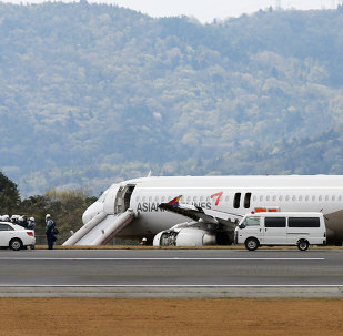 An Asiana Airlines Airbus A320 aircraft is seen with its evacuation slides deployed after it overran a runway at the Hiroshima airport in Mihara in Hirishima prefecture, western Japan