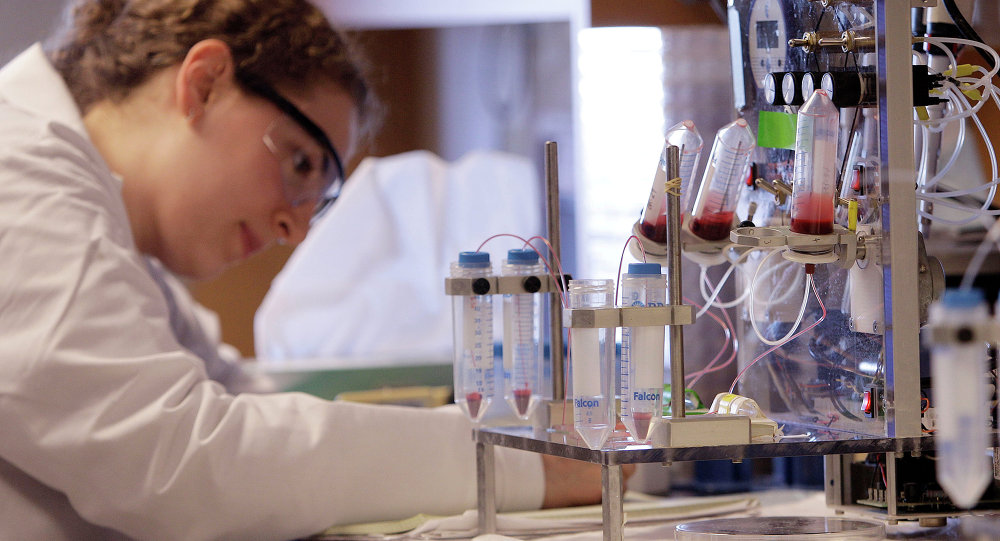 A researcher works near a blood test machine