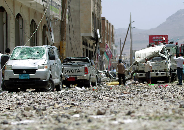 Yemeni men check a damaged street following a raid by Saudi-led coalition warplanes on a nearby missile depot on Fajj Attan hill, in the rebel-held part of the Yemeni capital, in southern Sanaa, on April 20, 2015