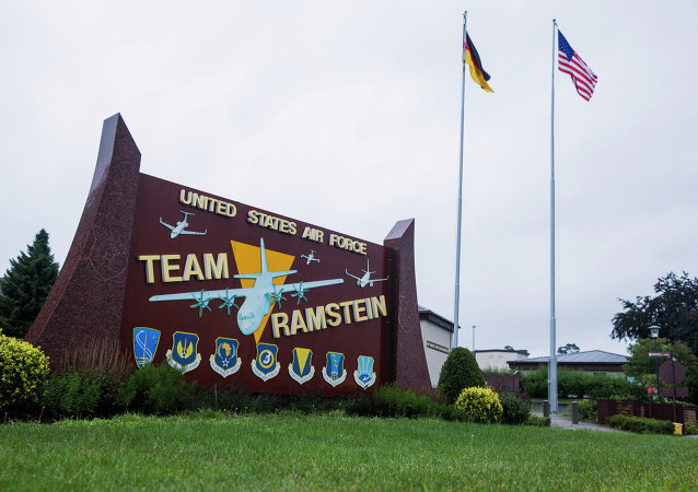 The flags of the United States and Germany fly behind a sign at Ramstein Air Base, Germany.