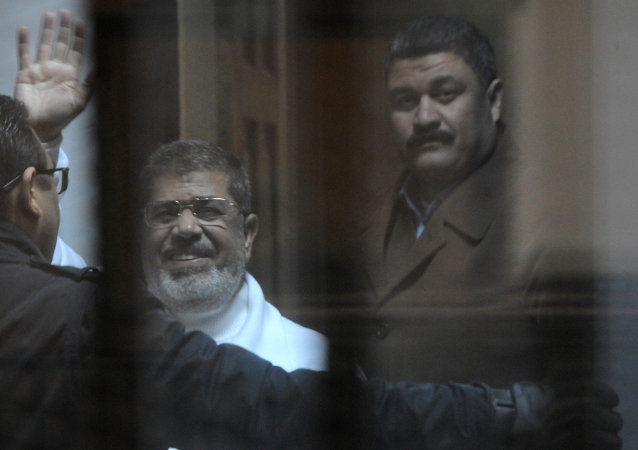 Egypt's deposed Islamist president Mohamed Morsi (L) waves from inside the defendant's cage during his trial at the police academy in Cairo