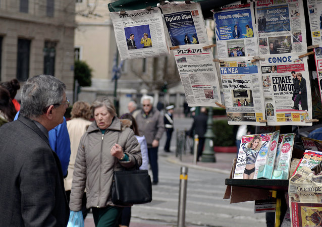 A man reads newspapers' headlines in Athens on March 24, 2015